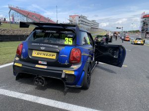 Mini on track with car door open